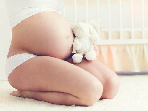 Pregnant woman holding a stuffed animal, artificial insemination can help you get pregnant.
