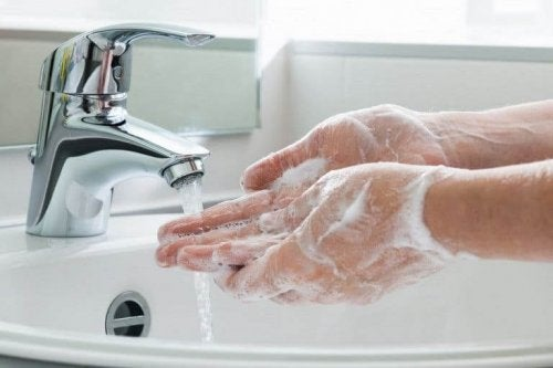 Soapy hands under running water from a tap.