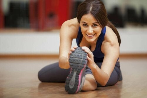 Woman in a gym stretching doing exercise to prevent nervous breakdowns