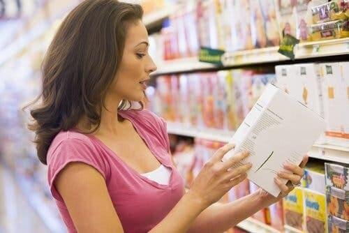 A woman reading a nutrition facts label.