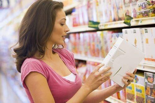 Woman reading product ingredients in grocery store.