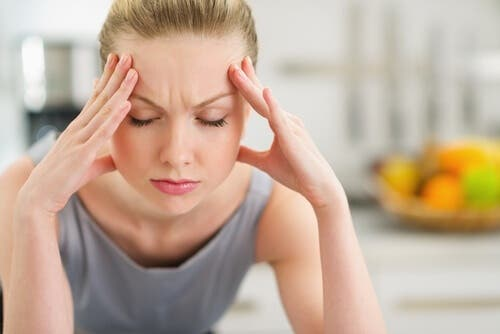 Woman with head in hands, stress can trigger migraine attacks.