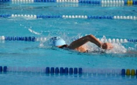 A woman swimming laps in a pool.