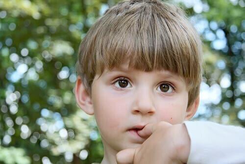 A boy biting his nails.