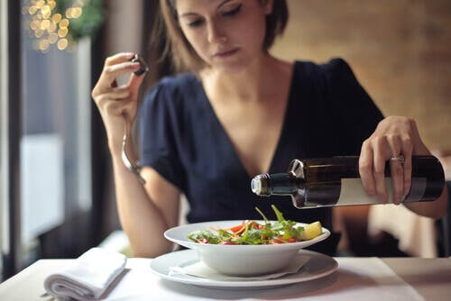 A woman adding olive oil in the salad. This can help improve your night routine