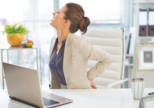 Woman sitting at desk, holding back in pain due to degenerative disc disease.