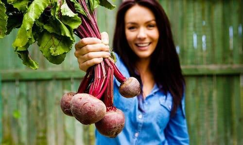 A woman holding beets.