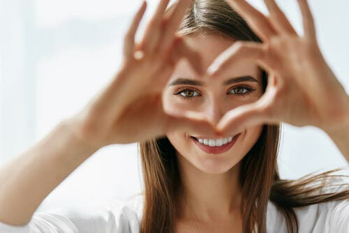 A woman making a heart with her hands.