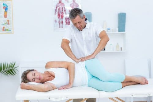 A woman being treated by a massage therapist for gluteal tendinopathy.