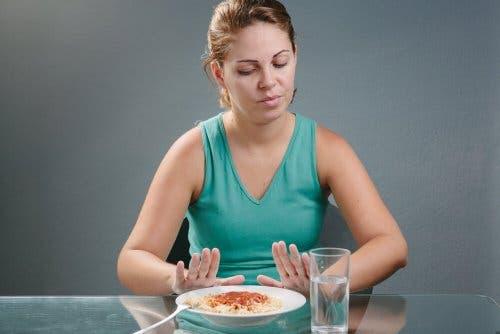 Woman on satiating diet refusing food.