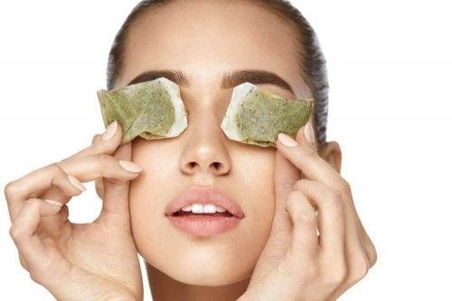 Woman putting tea bags on eyes to reduce eye pain.