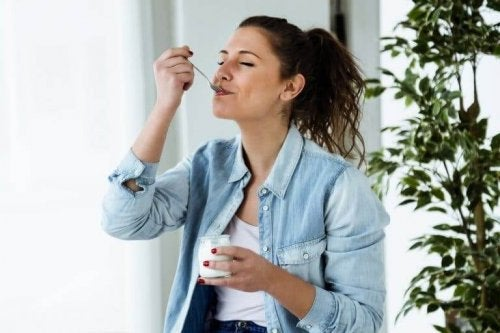 Woman eating a yogurt.