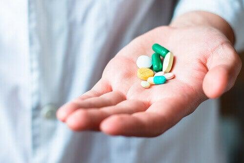 A hand holding pills.