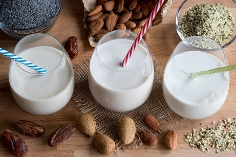 Three glasses of almond milk with different nuts around.
