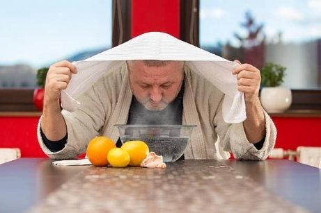 Man with towel over head inhaling steam to cure a sinus headache.
