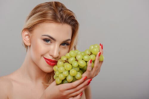 A pretty woman holding a bunch of grapes.