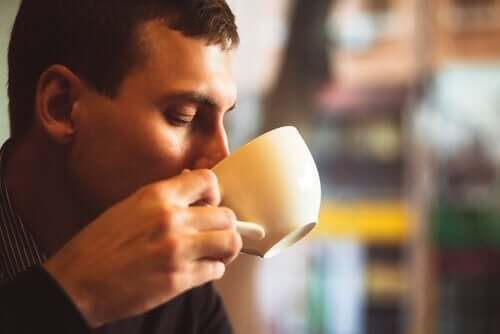 A man drinking a cup of coffee.