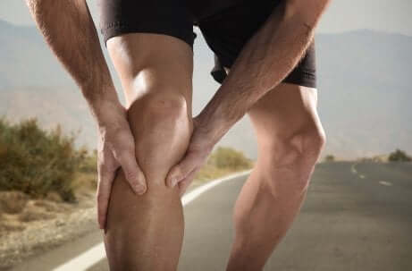 Man on road holding leg due to a muscle cramp.