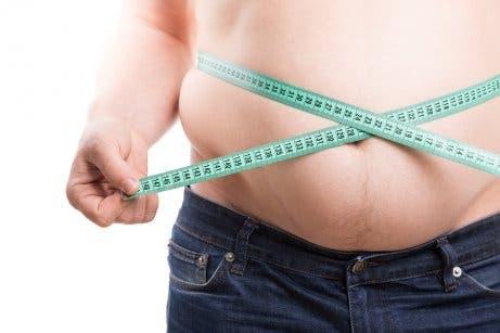 Man measuring waist with tape measure.
