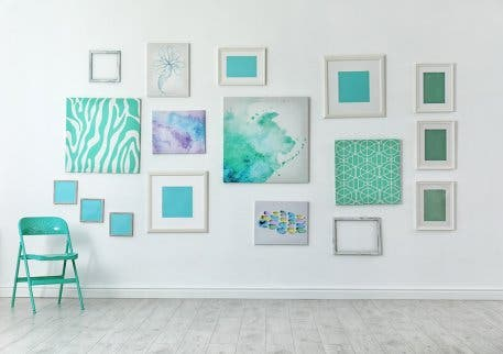 Different sized blue photos and paintings to decorate a wall.