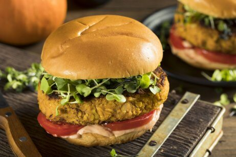 Veggie burgers made with pumpkin with greens and tomato.