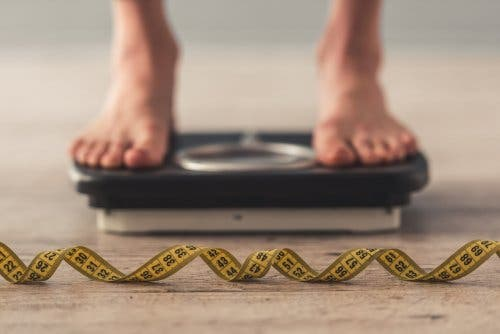 Feet standing on scale, tape measure on floor. Eliminating fat doesn't help weight loss.