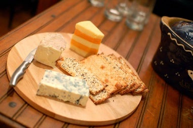 Different cheeses and crackers on a cutting board.