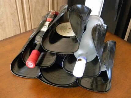 Wine bottle rack made out of vinyl records.