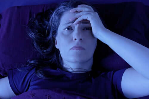 Woman laying in bed awake with her hand on her head.