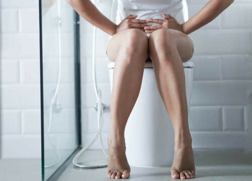 Woman on toilet with diarrhea from salmonellosis.