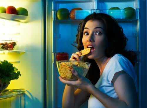 A woman eating by the fridge.