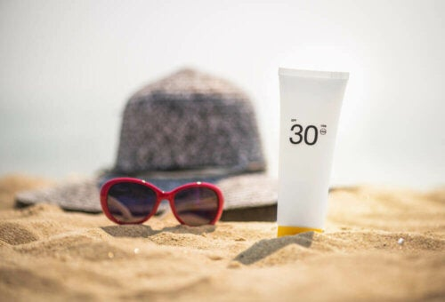 Hat, sunglasses, and sunblock tube sitting on the sand.
