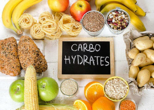 "Different sources of carbohydrates around chalkboard that says ""carbohydrates""."