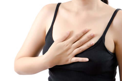 A woman touching her chest.