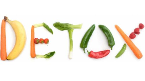 "Fruits and vegetables arranged on a white background to spell ""DETOX""."