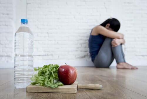 Woman sitting on floor hugging knees to chest with lettuce, apple, and water in the foreground.
