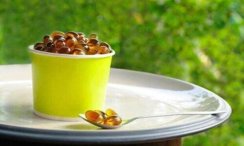 Lecithin supplement capsules in a container and on a spoon.