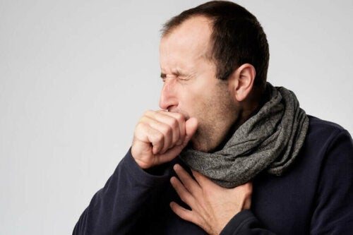 Man wearing a scarf coughing into hand.
