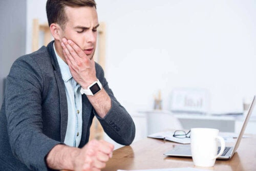 Man in office holding jaw.
