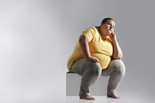 Obese woman sitting on a box with poor postural hygiene.