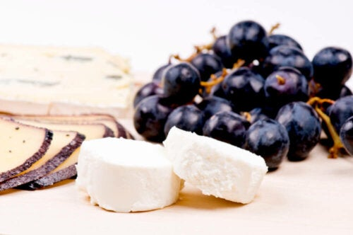Cheese and grapes on a cutting board.
