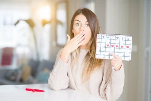 Surprised woman holding up calendar marking her menstrual cycle.