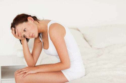 Woman in white sitting in bed, treat urinary tract infections early to avoid complications.
