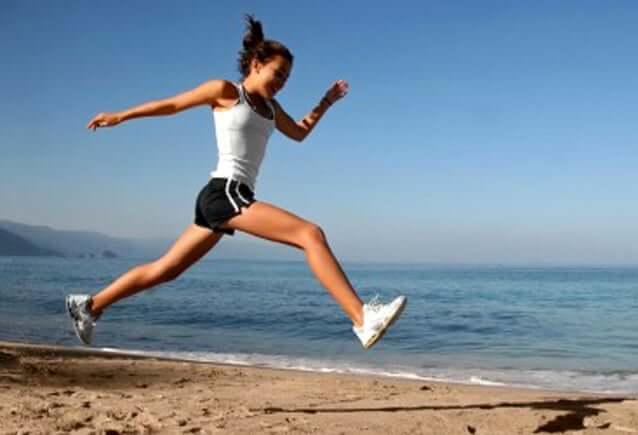 A woman leaping on the beach.