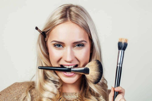 Woman with makeup brushes in teeth, behind ear, and in hand.