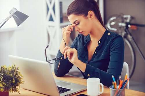 Woman in office in front of laptop facing daily stress.