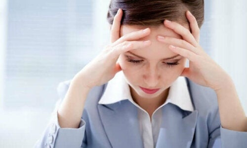 Stressed woman with her head in her hands, if you worry about your health too much it's harmful.
