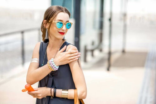 Woman putting sunblock on arm to prevent solar erythema.