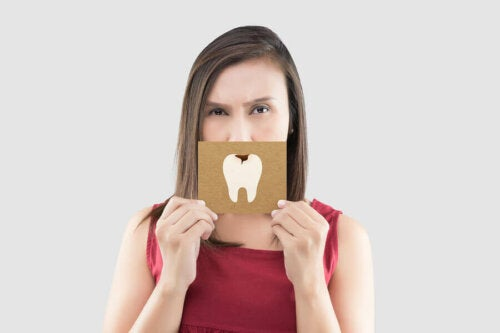 Woman holding a sign with a tooth with a cavity on it in front of her mouth.
