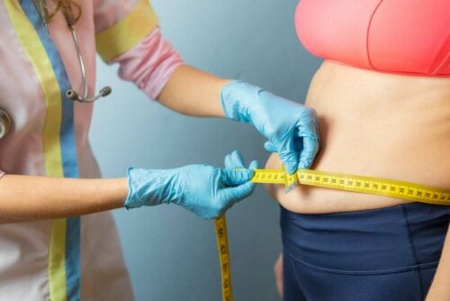 A doctor measuring an overweight person.